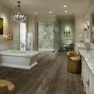 На фото: класса люкс огромные главные ванные комнаты в классическом стиле с плоскими фасадами, фасадами цвета дерева среднего тона, накладной ванной, двойным душем, унитазом-моноблоком, бежевой плиткой, каменной плиткой, бежевыми стенами, полом из керамогранита, монолитной раковиной и столешницей из гранита