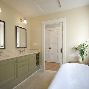 Diseño de cuarto de baño principal, clásico, grande, con armarios con paneles empotrados, puertas de armario verdes, bañera exenta, paredes amarillas, suelo de travertino, lavabo bajoencimera, encimera de mármol y suelo beige