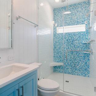 Diseño de cuarto de baño principal, costero, pequeño, con armarios estilo shaker, puertas de armario azules, ducha empotrada, baldosas y/o azulejos azules, baldosas y/o azulejos en mosaico, paredes blancas, lavabo bajoencimera, suelo blanco y encimeras blancas