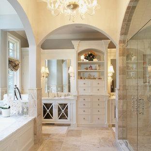 На фото: ванная комната в классическом стиле с белыми фасадами, душем в нише, бежевой плиткой и плиткой из известняка