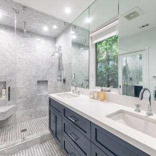 Источник вдохновения для домашнего уюта: большая главная ванная комната в стиле неоклассика (современная классика) с фасадами в стиле шейкер, синими фасадами, душем в нише, унитазом-моноблоком, серой плиткой, керамогранитной плиткой, белыми стенами, мраморным полом, врезной раковиной, столешницей из искусственного кварца, душем с распашными дверями, белой столешницей, сиденьем для душа, тумбой под две раковины, подвесной тумбой и серым полом