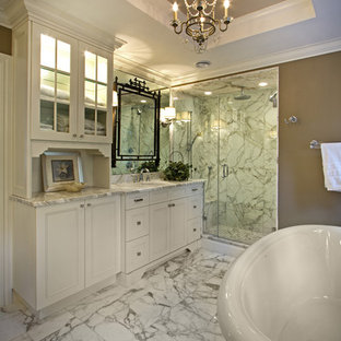 Elegant white tile and marble tile bathroom photo in New York with an undermount sink and white cabinets