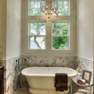 Foto de cuarto de baño principal, tradicional renovado, grande, con armarios estilo shaker, puertas de armario de madera en tonos medios, encimera de piedra caliza, bañera exenta, baldosas y/o azulejos grises y suelo de piedra caliza