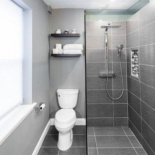 Foto på ett litet funkis en-suite badrum, med en kantlös dusch, en toalettstol med separat cisternkåpa, grå kakel, keramikplattor, grå väggar och klinkergolv i keramik