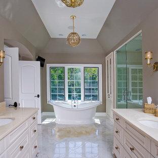 Foto på ett stort vintage en-suite badrum, med ett undermonterad handfat, beige skåp, ett fristående badkar, en dusch i en alkov, vit kakel, stenkakel, bruna väggar, marmorgolv, marmorbänkskiva och luckor med upphöjd panel