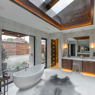 Inspiration for a huge contemporary master gray tile freestanding bathtub remodel in Dallas with flat-panel cabinets, medium tone wood cabinets, an urinal and a hinged shower door