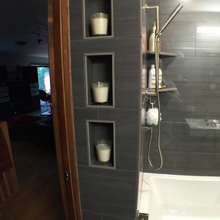 Example of a mid-sized trendy master black tile and porcelain tile bathroom design in Portland with solid surface countertops, a one-piece toilet, black walls, flat-panel cabinets and an integrated sink