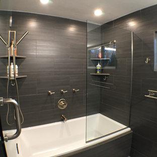 Inspiration för mellanstora moderna en-suite badrum, med bänkskiva i akrylsten, ett badkar i en alkov, en dusch/badkar-kombination, en toalettstol med hel cisternkåpa, svart kakel, porslinskakel och svarta väggar