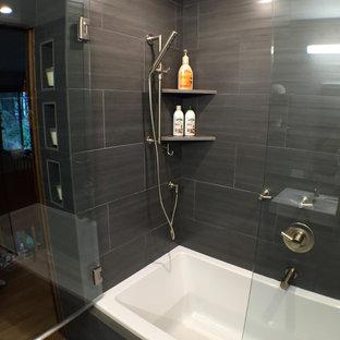 ポートランドの中くらいのコンテンポラリースタイルのおしゃれなマスターバスルーム (コンソール型シンク、人工大理石カウンター、アルコーブ型浴槽、シャワー付き浴槽、一体型トイレ、黒いタイル、磁器タイル、黒い壁) の写真