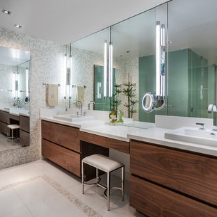 Example of a large trendy master beige tile and mosaic tile ceramic tile and beige floor corner shower design in Miami with a vessel sink, flat-panel cabinets, multicolored walls, solid surface countertops, dark wood cabinets, a two-piece toilet and a hinged shower door