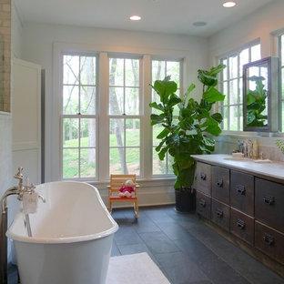 Diseño de cuarto de baño actual con lavabo bajoencimera, armarios con paneles lisos, puertas de armario con efecto envejecido, bañera exenta, baldosas y/o azulejos grises y suelo de pizarra