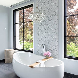 Inspiration for a classic bathroom in Milwaukee with a freestanding bath, grey walls and brown floors.