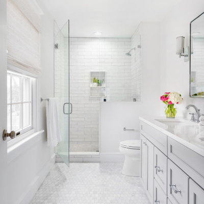 Mid-sized transitional master porcelain tile and white tile marble floor and white floor alcove shower photo in Philadelphia with gray cabinets, white walls, a hinged shower door, recessed-panel cabinets, an undermount sink and white countertops