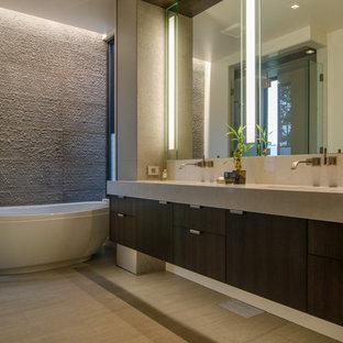 Esempio di una stanza da bagno padronale contemporanea di medie dimensioni con ante lisce, ante in legno bruno, vasca freestanding, piastrelle beige, piastrelle in pietra, pareti multicolore, pavimento in gres porcellanato, lavabo sottopiano, top in pietra calcarea e pavimento beige