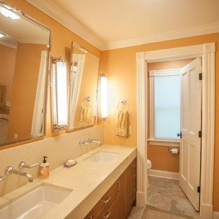 Idee per una grande stanza da bagno padronale chic con ante lisce, ante in legno scuro, vasca ad alcova, doccia alcova, WC monopezzo, piastrelle grigie, lastra di pietra, pareti arancioni, pavimento in ardesia, lavabo sottopiano e top in quarzite
