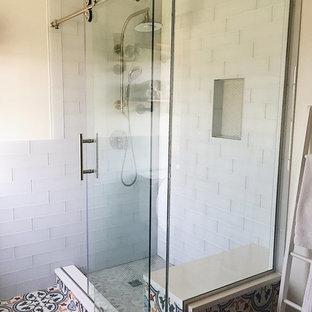 50 tals inredning av ett mellanstort röd rött en-suite badrum, med luckor med infälld panel, skåp i mörkt trä, en öppen dusch, en toalettstol med separat cisternkåpa, vit kakel, kakelplattor, vita väggar, klinkergolv i keramik, ett väggmonterat handfat, granitbänkskiva, flerfärgat golv och dusch med skjutdörr