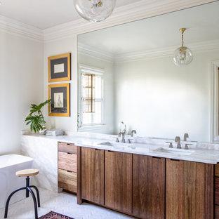 Ejemplo de cuarto de baño principal, tradicional renovado, grande, con armarios con paneles lisos, puertas de armario de madera en tonos medios, bañera exenta, baldosas y/o azulejos blancos, losas de piedra, paredes blancas, lavabo bajoencimera, encimera de mármol y suelo de mármol