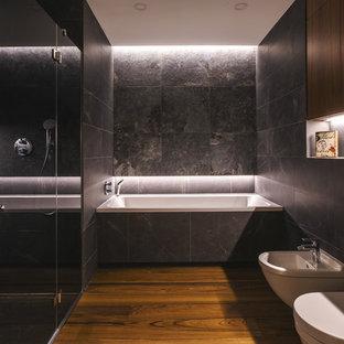 На фото: со средним бюджетом главные ванные комнаты среднего размера в современном стиле с плоскими фасадами, фасадами цвета дерева среднего тона, душем в нише, раздельным унитазом, черной плиткой, керамической плиткой, темным паркетным полом, врезной раковиной, столешницей из искусственного кварца, оранжевым полом, душем с распашными дверями и белой столешницей