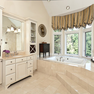 Inspiration for a large timeless master beige tile and marble tile marble floor and beige floor bathroom remodel in Baltimore with an undermount sink, recessed-panel cabinets, beige cabinets, beige walls and marble countertops