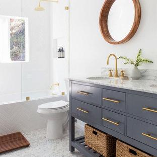 Пример оригинального дизайна: маленькая главная ванная комната в морском стиле с фасадами островного типа, синими фасадами, накладной ванной, душем над ванной, унитазом-моноблоком, белой плиткой, плиткой кабанчик, белыми стенами, полом из мозаичной плитки, врезной раковиной, мраморной столешницей, белым полом, открытым душем и белой столешницей