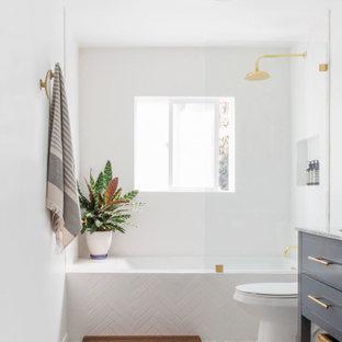 Inspiration för ett litet maritimt vit vitt en-suite badrum, med möbel-liknande, blå skåp, ett platsbyggt badkar, en dusch/badkar-kombination, en toalettstol med hel cisternkåpa, vit kakel, tunnelbanekakel, vita väggar, mosaikgolv, ett undermonterad handfat, marmorbänkskiva, vitt golv och med dusch som är öppen