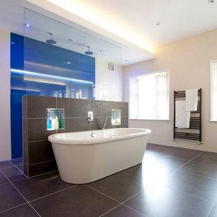 Idee per un'ampia stanza da bagno padronale contemporanea con lavabo a bacinella, ante lisce, ante in legno scuro, top in vetro, vasca freestanding, doccia doppia, WC a due pezzi, piastrelle marroni, piastrelle in gres porcellanato, pareti blu e pavimento in gres porcellanato