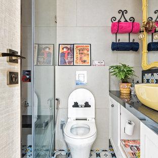 Réalisation d'une salle de bain bohème avec une douche à l'italienne, un WC suspendu, un mur gris, une vasque et un sol multicolore.