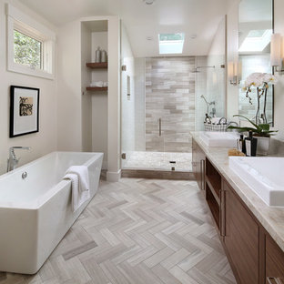 サンフランシスコの中サイズのコンテンポラリースタイルのおしゃれなマスターバスルーム (フラットパネル扉のキャビネット、中間色木目調キャビネット、置き型浴槽、アルコーブ型シャワー、グレーのタイル、磁器タイル、白い壁、磁器タイルの床、ベッセル式洗面器、珪岩の洗面台、ベージュの床、ベージュのカウンター) の写真