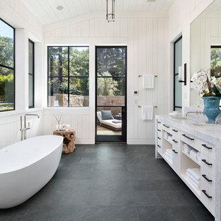Diseño de cuarto de baño principal, de estilo de casa de campo, con armarios abiertos, puertas de armario blancas, bañera exenta, paredes blancas, lavabo bajoencimera, suelo gris, suelo de pizarra y encimera de mármol
