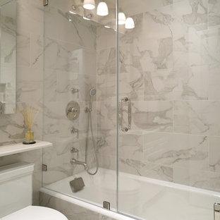 ニューヨークの小さいトラディショナルスタイルのおしゃれなマスターバスルーム (アンダーカウンター洗面器、レイズドパネル扉のキャビネット、白いキャビネット、ドロップイン型浴槽、シャワー付き浴槽、一体型トイレ、白いタイル、磁器タイル、白い壁、磁器タイルの床、珪岩の洗面台) の写真