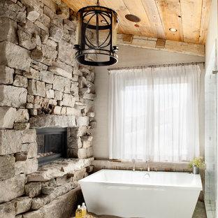 Foto de cuarto de baño rústico con bañera exenta, losas de piedra, paredes beige, suelo de madera en tonos medios y encimera de mármol
