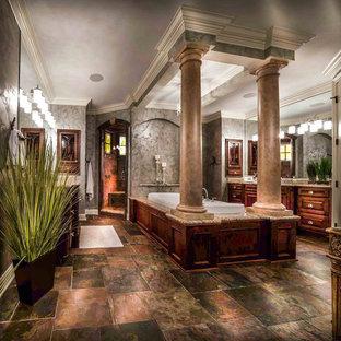 Eklektisk inredning av ett mycket stort en-suite badrum, med luckor med profilerade fronter, skåp i mellenmörkt trä, granitbänkskiva, ett platsbyggt badkar, en öppen dusch, flerfärgad kakel, stenkakel, grå väggar och skiffergolv