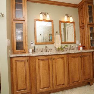 セントルイスの大きいトラディショナルスタイルのおしゃれなマスターバスルーム (アンダーカウンター洗面器、レイズドパネル扉のキャビネット、中間色木目調キャビネット、クオーツストーンの洗面台、猫足浴槽、ベージュのタイル、セラミックタイル、緑の壁、セラミックタイルの床) の写真