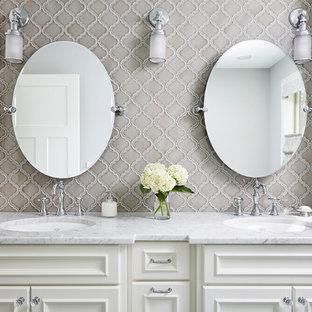 Ejemplo de cuarto de baño principal, tradicional, grande, con armarios con paneles empotrados, puertas de armario blancas, baldosas y/o azulejos grises, baldosas y/o azulejos de porcelana, paredes grises, lavabo bajoencimera, encimera de acrílico y encimeras grises