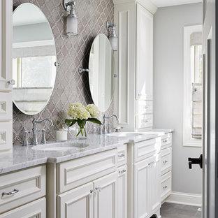 Modelo de cuarto de baño principal, clásico, grande, con armarios con paneles empotrados, puertas de armario blancas, baldosas y/o azulejos grises, baldosas y/o azulejos de porcelana, encimera de acrílico, encimeras grises, ducha esquinera, sanitario de dos piezas, paredes grises, suelo de baldosas de cerámica, lavabo bajoencimera, suelo gris y ducha con puerta con bisagras