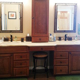 Medium sized mediterranean ensuite bathroom in Denver with raised-panel cabinets, medium wood cabinets, a corner shower, a two-piece toilet, beige tiles, travertine tiles, beige walls, medium hardwood flooring, a submerged sink, marble worktops, brown floors and an open shower.