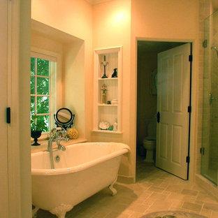 Diseño de cuarto de baño principal, clásico, de tamaño medio, con puertas de armario blancas, bañera con patas, ducha esquinera, sanitario de dos piezas, baldosas y/o azulejos beige, baldosas y/o azulejos de piedra, paredes amarillas y suelo de travertino
