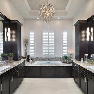 Großes Klassisches Badezimmer En Suite mit Schrankfronten im Shaker-Stil, dunklen Holzschränken, beigefarbenen Fliesen, Fliesen aus Glasscheiben, weißer Wandfarbe, Unterbauwaschbecken, Granit-Waschbecken/Waschtisch, Unterbauwanne, Porzellan-Bodenfliesen und beigem Boden in Miami
