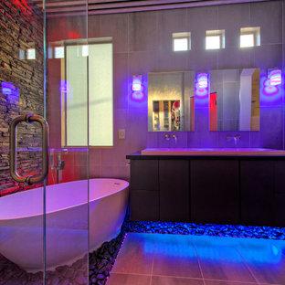 Inspiration för ett mellanstort funkis en-suite badrum, med släta luckor, skåp i mörkt trä, ett fristående badkar, en hörndusch, en toalettstol med hel cisternkåpa, grå kakel, porslinskakel, grå väggar, klinkergolv i porslin, ett väggmonterat handfat och bänkskiva i akrylsten