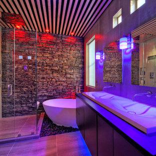 Пример оригинального дизайна интерьера: главная ванная комната среднего размера в современном стиле с плоскими фасадами, темными деревянными фасадами, отдельно стоящей ванной, угловым душем, серой плиткой, серыми стенами, столешницей из искусственного камня, раковиной с несколькими смесителями и душем с распашными дверями
