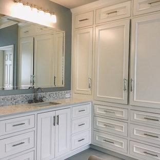 Klassisk inredning av ett stort grå grått en-suite badrum, med luckor med upphöjd panel, vita skåp, ett fristående badkar, en kantlös dusch, en toalettstol med separat cisternkåpa, vit kakel, marmorkakel, grå väggar, klinkergolv i keramik, ett undermonterad handfat, bänkskiva i kvartsit, grått golv och dusch med gångjärnsdörr