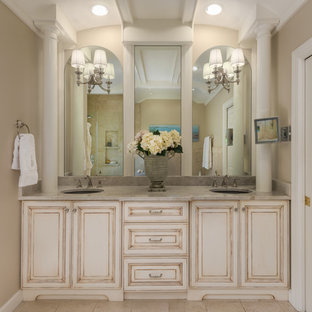 Design ideas for a large mediterranean ensuite bathroom in St Louis with raised-panel cabinets, beige cabinets, a submerged bath, a corner shower, a two-piece toilet, beige tiles, marble tiles, beige walls, marble flooring, a submerged sink, marble worktops, beige floors, a hinged door and beige worktops.