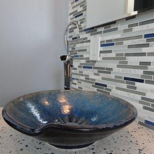 Diseño de cuarto de baño actual, de tamaño medio, con lavabo sobreencimera, armarios tipo vitrina, puertas de armario de madera en tonos medios, encimera de cuarcita, ducha a ras de suelo, sanitario de una pieza, baldosas y/o azulejos marrones, paredes azules y suelo de baldosas de porcelana