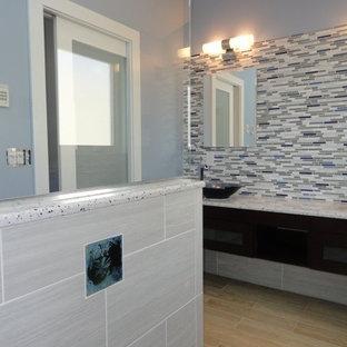 Foto de cuarto de baño contemporáneo, de tamaño medio, con lavabo sobreencimera, armarios tipo vitrina, puertas de armario de madera en tonos medios, encimera de cuarcita, ducha a ras de suelo, sanitario de una pieza, baldosas y/o azulejos marrones, paredes azules y suelo de baldosas de porcelana