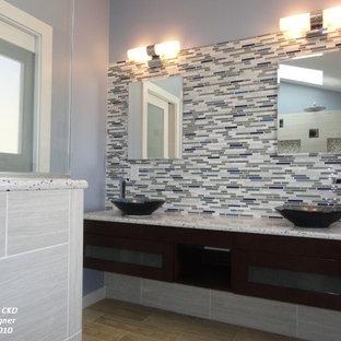 Imagen de cuarto de baño actual, de tamaño medio, con lavabo sobreencimera, armarios tipo vitrina, puertas de armario de madera en tonos medios, encimera de cuarcita, ducha a ras de suelo, sanitario de una pieza, baldosas y/o azulejos marrones, paredes azules y suelo de baldosas de porcelana