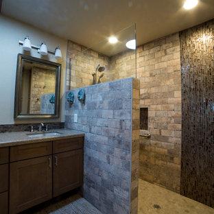 フェニックスの広いラスティックスタイルのおしゃれなマスターバスルーム (落し込みパネル扉のキャビネット、中間色木目調キャビネット、バリアフリー、マルチカラーのタイル、磁器タイル、ベージュの壁、磁器タイルの床、アンダーカウンター洗面器、珪岩の洗面台、ベージュの床、オープンシャワー、ベージュのカウンター) の写真