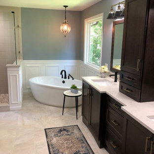 This is an example of a mid-sized transitional master bathroom in Cincinnati with shaker cabinets, dark wood cabinets, a freestanding tub, beige tile, porcelain tile, grey walls, ceramic floors, an undermount sink, quartzite benchtops, beige floor, a hinged shower door and turquoise benchtops.