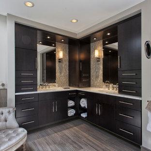ニューヨークの大きいコンテンポラリースタイルのおしゃれなマスターバスルーム (アンダーカウンター洗面器、フラットパネル扉のキャビネット、濃色木目調キャビネット、大理石の洗面台、置き型浴槽、オープン型シャワー、分離型トイレ、メタルタイル、茶色い壁、磁器タイルの床、ベージュのタイル) の写真