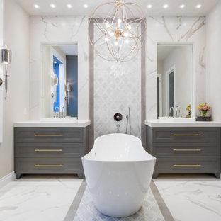 ヒューストンの中くらいのトランジショナルスタイルのおしゃれなマスターバスルーム (家具調キャビネット、グレーのキャビネット、置き型浴槽、白いタイル、磁器タイル、グレーの壁、大理石の床、珪岩の洗面台、バリアフリー、壁掛け式トイレ、ベッセル式洗面器) の写真