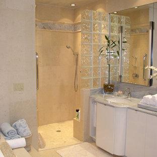 На фото: главная ванная комната среднего размера в морском стиле с плоскими фасадами, белыми фасадами, гидромассажной ванной, душем в нише, бежевой плиткой, плиткой из травертина, бежевыми стенами, полом из травертина, врезной раковиной, бежевым полом, открытым душем, столешницей из кварцита и серой столешницей с